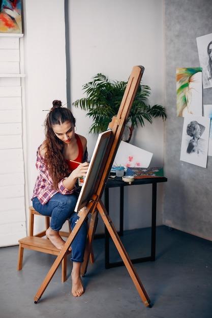 Elegant girl draws in an art studio Free Photo
