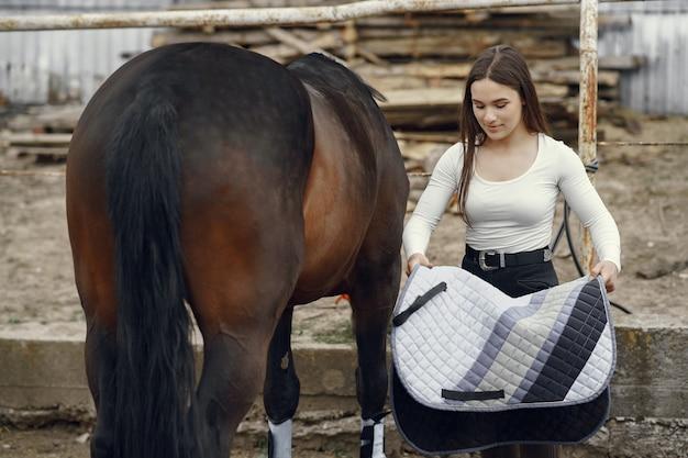 Elegant girl in a farm wiith a horse Free Photo