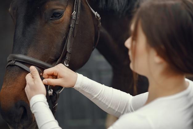 Ragazza elegante in una fattoria con un cavallo Foto Gratuite