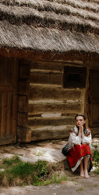 Elegant girl in a traditional dress sitting next to the house Free Photo