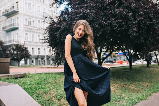 Elegante ragazza con i capelli lunghi e le labbra vinose è in posa nel parco di ciyu. Foto Gratuite
