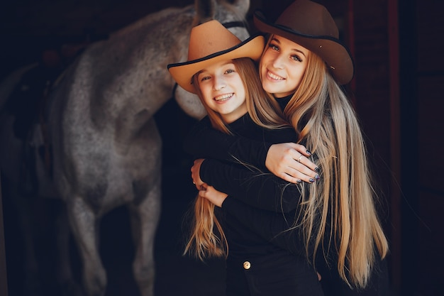Elegant girls with a horse in a ranch Free Photo
