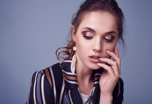 Шикарная женщина очарования в модном костюме представляя на красочной сини Premium Фотографии