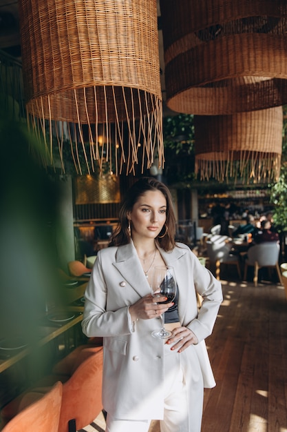 Elegant and glamour woman with glass of red wine in restaurant. Premium Photo