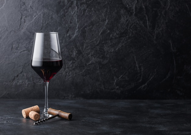 Elegant glass of red wine with corks and corkscrew on black stone background. Premium Photo