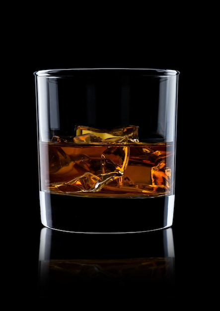 Elegant glass of whiskey with ice cubes on black background with reflection Premium Photo