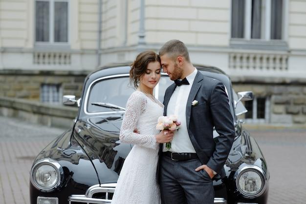 エレガントなゴージャスな花嫁とハンサムな新郎が光の中でスタイリッシュな黒い車を受け入れます。 Premium写真