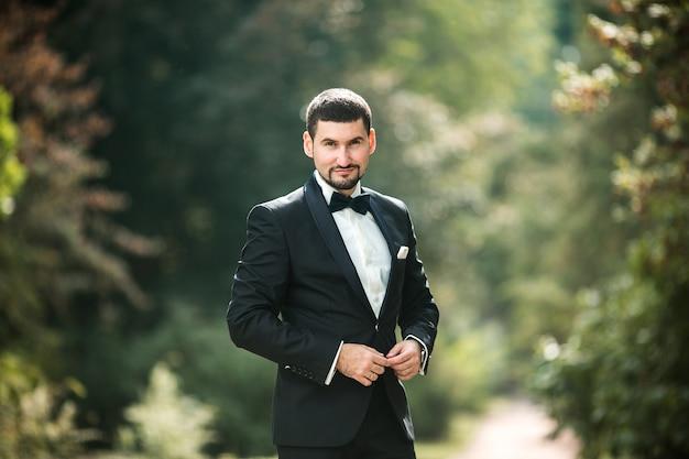 Elegant groom posing outdoors Free Photo
