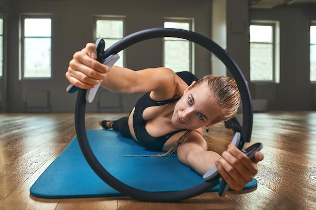 Элегантный учитель гимнастики перевернутыми руками поддерживает тело на полу, а ноги на кольце для пилатеса с растянутым телом развивают мягкость в студии на серой стене. Premium Фотографии