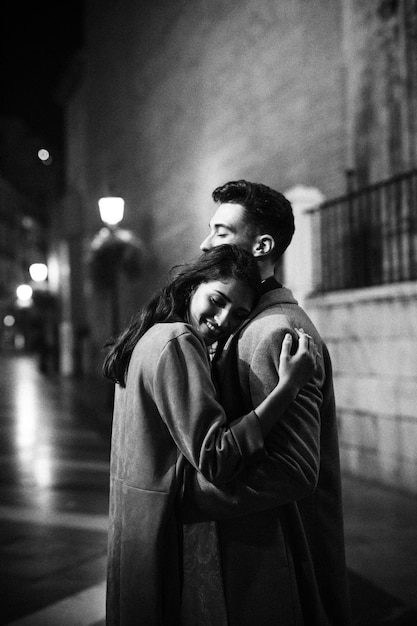 Elegant happy woman hugging with young man on street at night Free Photo