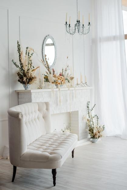 ヴィンテージのソファー、クリスタルのシャンデリア、暖炉の下の鏡が飾られたホワイトトーンのエレガントなインテリア。 Premium写真