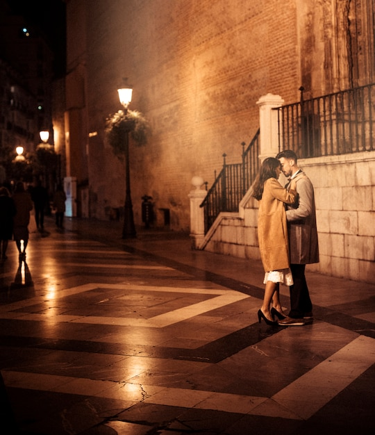 Elegant lady hugging and kissing with young guy on street Free Photo