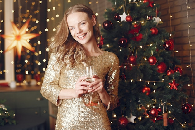 クリスマスツリーの近くのエレガントな女性。シャンパンで家にいる女性。 無料写真