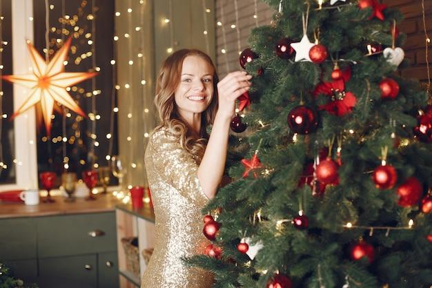 クリスマスツリーの近くのエレガントな女性。家にいる女性 無料写真