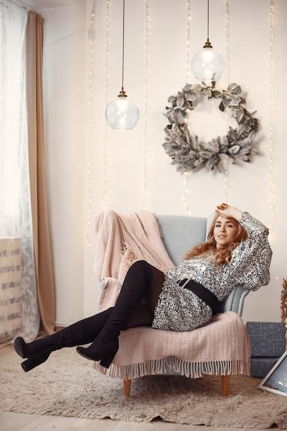 クリスマスツリーの近くのエレガントな女性。部屋の女性。銀のドレスを着た女性。 無料写真
