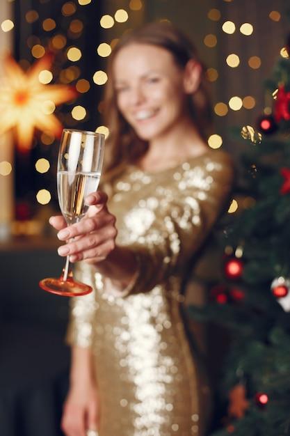 Элегантная дама возле елки. женщина дома с шампанским. Бесплатные Фотографии