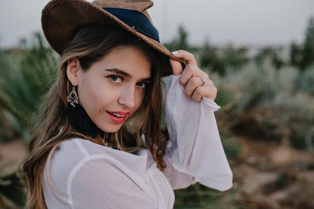 美しいエキゾチックな公園を歩きながら、スタイリッシュな帽子でエレガントな長い髪の女性に見えます。トレンディなイヤリングと謎の表情でポーズのシャツでかなり若い女性のクローズアップの肖像画 無料写真