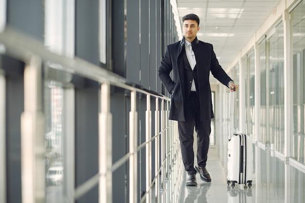 スーツケースを空港でエレガントな男 無料写真