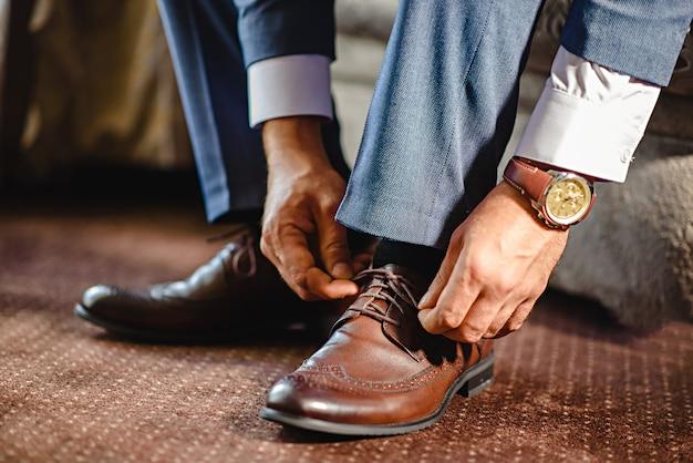 An elegant man puts on black, leather, formal shoes. Premium Photo