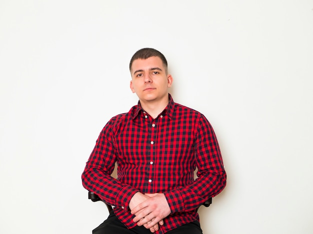 Elegant man siting and posing on brown background. Premium Photo