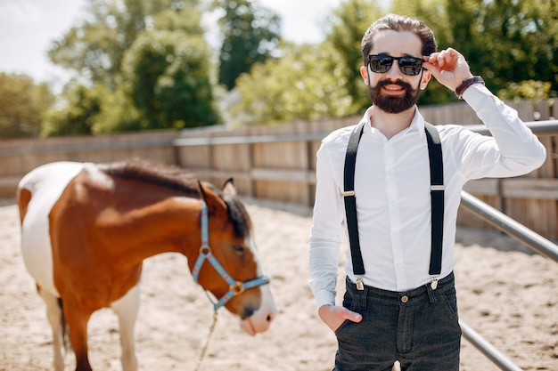 Elegant man standing next to horse in a ranch Free Photo