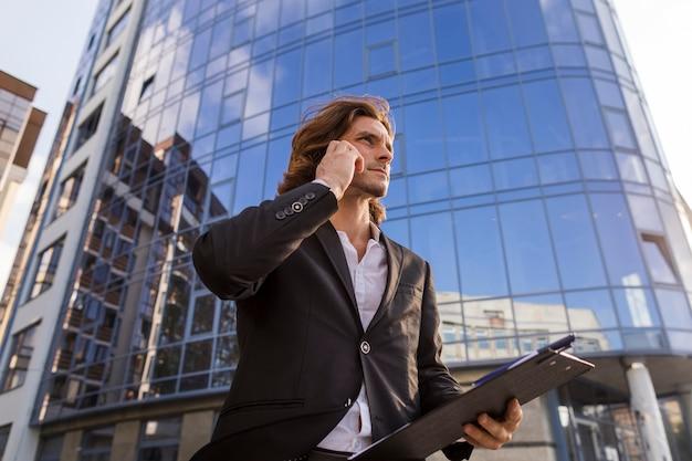 Elegant man talking at phone low angle shot Free Photo