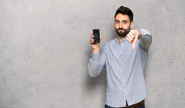 Elegant man with shirt with troubled holding broken smartphone over textured wall Premium Photo