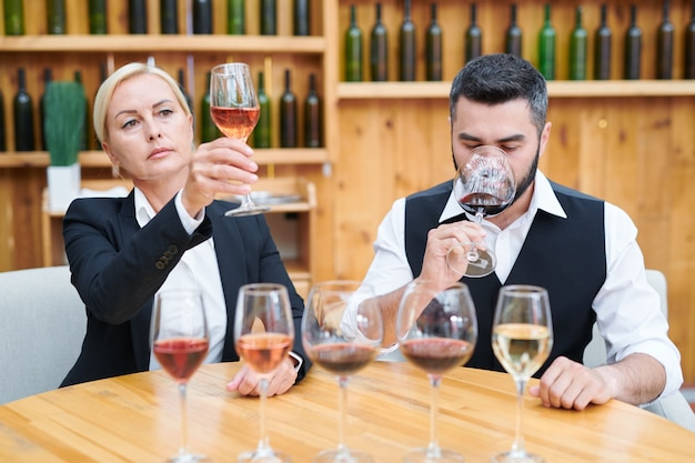 Elegant man and woman sitting by table in cellar while examining color, taste and smell of new sorts of wine Premium Photo