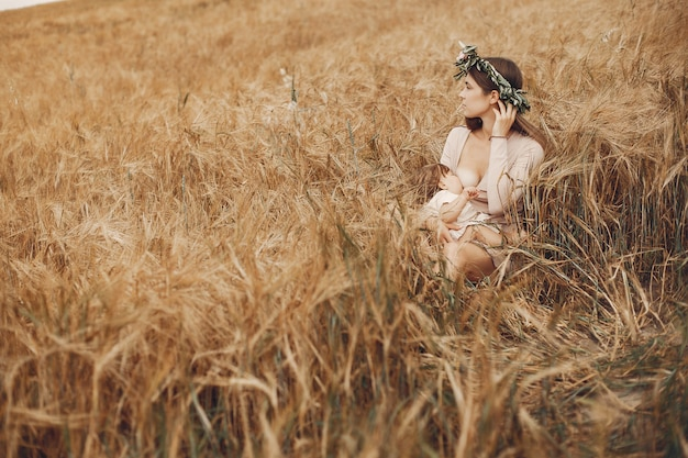 Elegant mother with cute little daughter in a field Free Photo