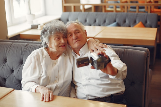 Elegant old couple in a cafe using a camera Free Photo