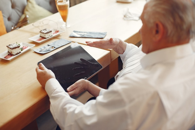 Elegant old couple in a cafe using a tablet Free Photo