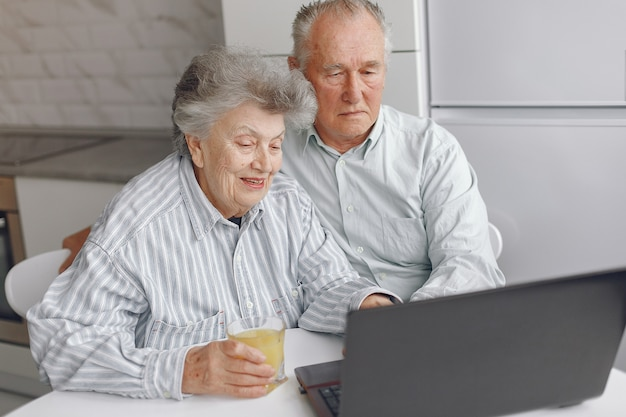 Elegant old couple sitting at home and using a laptop Free Photo