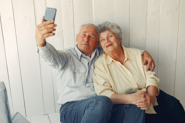 Elegant old couple sitting at home and using a phone Free Photo