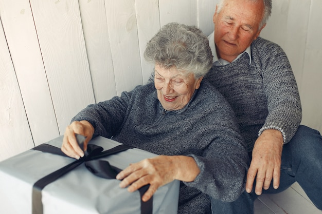 Elegant old couple sitting at home with christmas gifts Free Photo