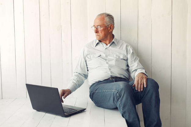 Elegant old man sitting at home and using a laptop Free Photo