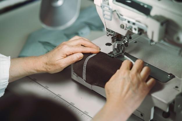 スタジオに座っているエレガントな老婦人と布を縫う 無料写真