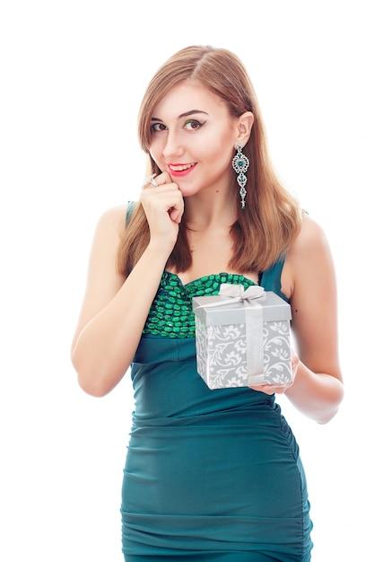 ダイヤモンドのイヤリングとリングを持つエレガントな優雅な女性。緑と白のダイヤモンドを使用したプラチナジュエリー。彼女の手に銀の箱でギフト Premium写真