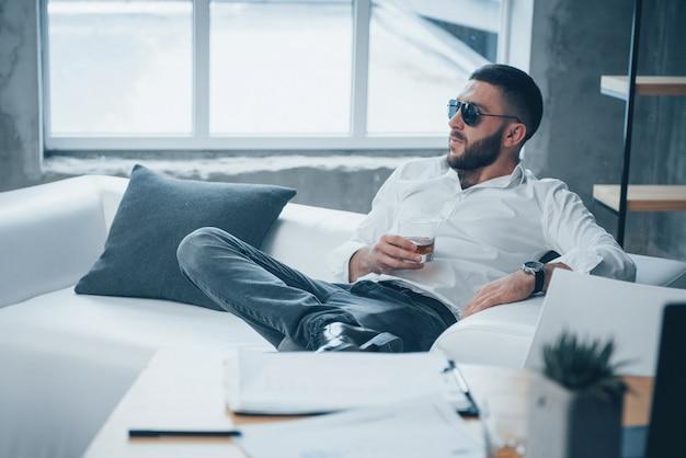Элегантная постановка. молодой короткошерстный мужчина в темных очках, сидя на диване в офисе Premium Фотографии