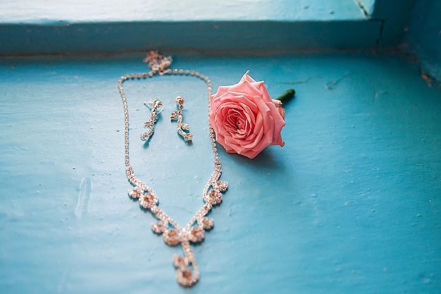 Elegant rose with necklace and earrings on a blue Premium Photo
