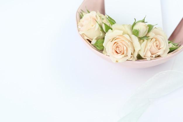Elegant roses in pink plate with invitation card Premium Photo