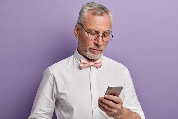우아한 수석 남자가 자신의 휴대 전화에서 일하고 디스플레이에 집중하여 현대 기술을 사용하는 방법을 이해하려고합니다. 무료 사진