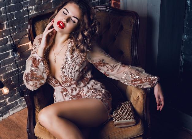 Elegante donna sensuale seduta in poltrona lussuosa Foto Gratuite