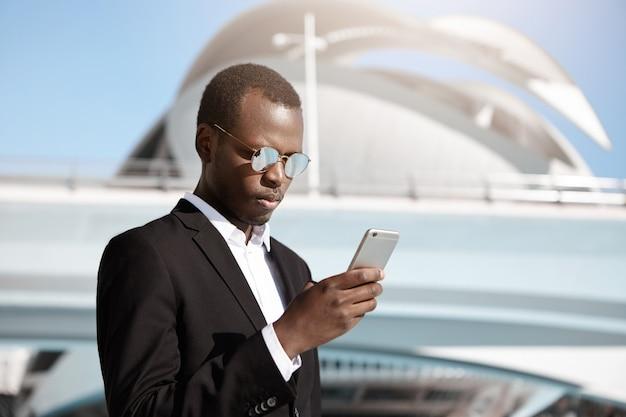 エレガントな深刻なアフリカ系アメリカ人の従業員が携帯電話で電子メールをチェック、晴れた夏の日に屋外でタクシー車を待っている間空港の近代的な建物の外に立って 無料写真