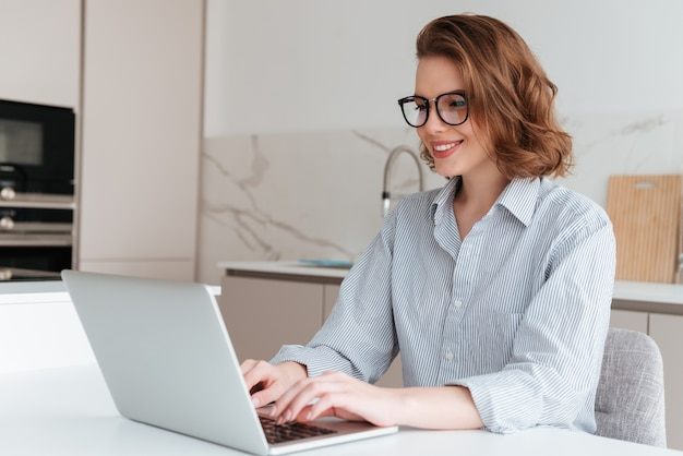 Elegant smiling woman in glasses and striped shirt using laptop computer while siting at table in kitchen Free Photo