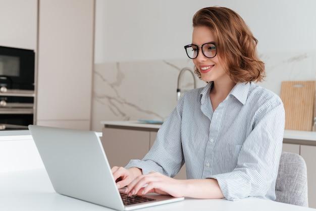 부엌에서 테이블에 Siting 동안 안경 및 스트라이프 셔츠에 우아한 웃는 여자 랩톱 컴퓨터를 사용 무료 사진