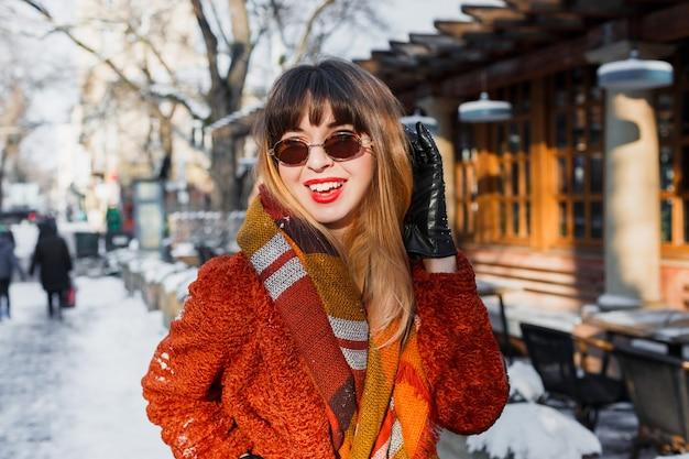 屋外ポーズレトロなメガネでエレガントな笑顔の女性 無料写真