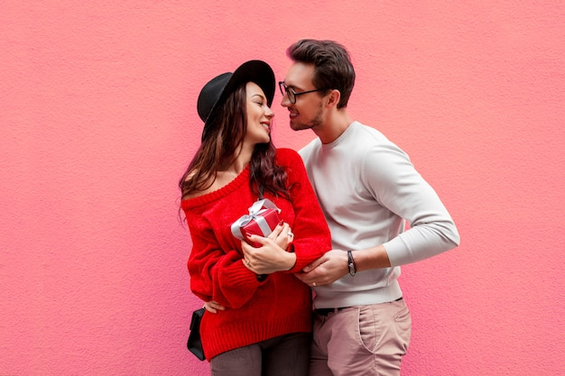 Elegant stylish couple in love holding hands and looking on each other with pleasure. long haired woman in red knitted sweater with her boyfriend posing. Free Photo
