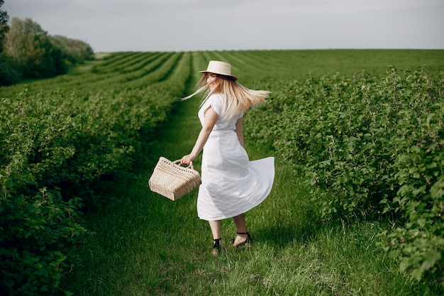 Elegant and stylish girl in a summer field Free Photo