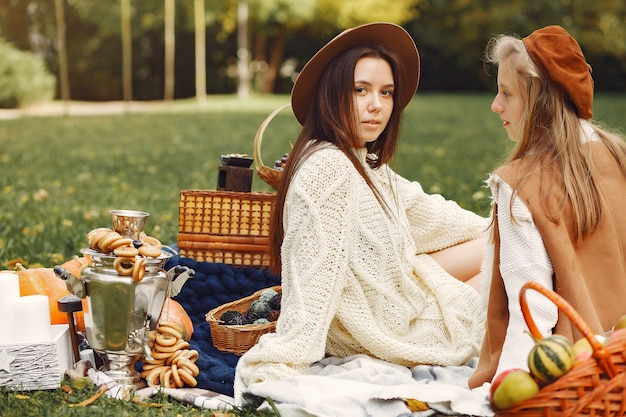 Elegant and stylish girls sitting in a autumn park Free Photo