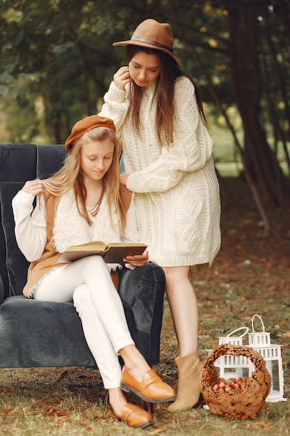 Elegant and stylish girls sitting on a chair in a park reading a book Free Photo